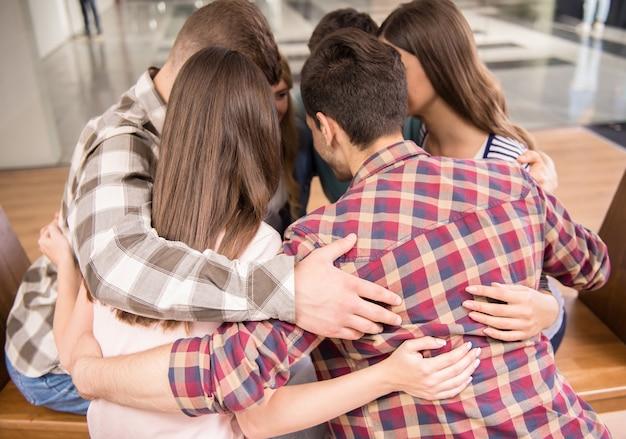 Groep mensen die in cirkel zitten en elkaar steunen.
