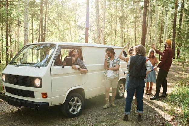 Groep mensen die in de buurt van het busje staan en op zoek zijn naar een verbinding op hun mobiele telefoon die in het bos staat