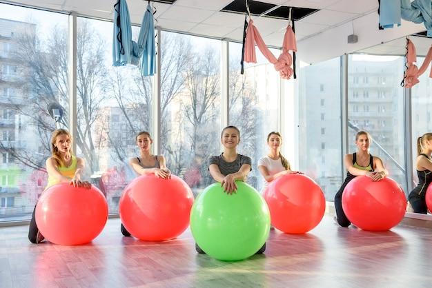 Groep mensen die in gymnastiek met een pilatesbal glimlachen