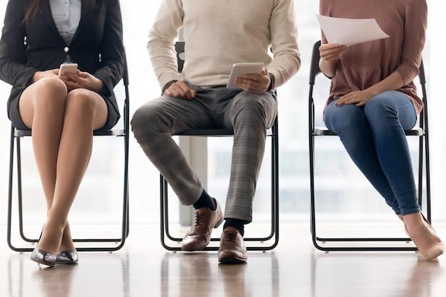 Groep mensen die op baangesprek wachten, zittend op stoelen