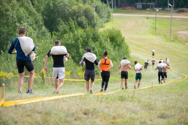 Groep mensen die oversteekplaats met zware zakken op hun schouders in de zomer zonnige dag in werking stellen