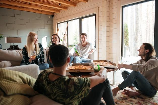 Groep mensen die pizza eten en in woonkamer ontspannen