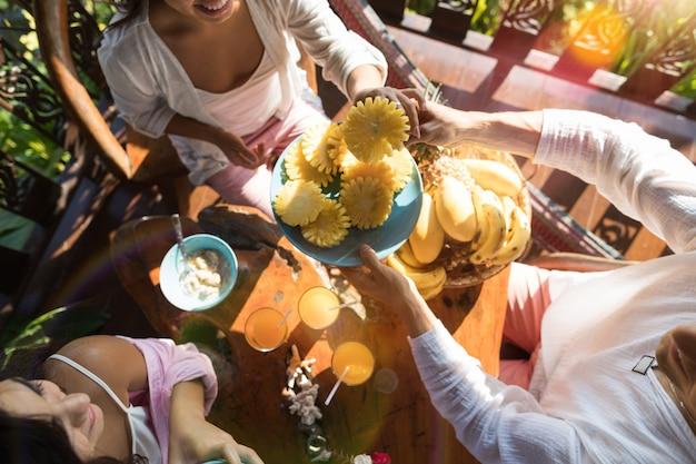 Groep mensen die samen ontbijt eten geniet van verse ananas