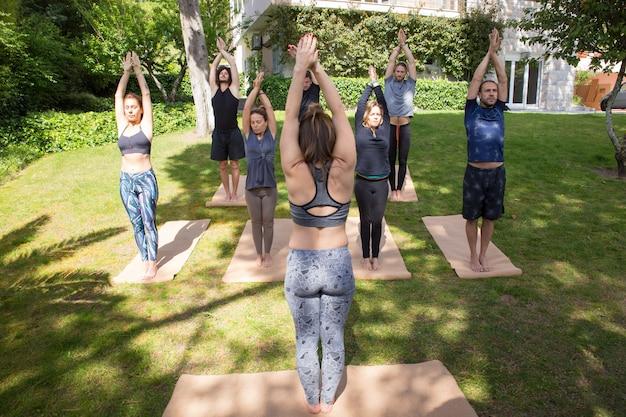Groep mensen die yoga doen dichtbij flatgebouw