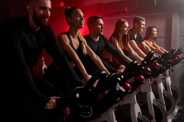 Groep mensen die zich bezighouden met een fietssimulator in de sportschool, trainen op een hometrainer, geïsoleerd in donkere neon verlichte rokerige ruimte. zijaanzicht
