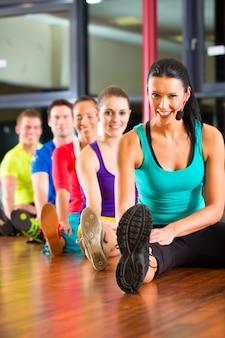 Groep mensen en instructeur in zich gymnastiek het uitrekken