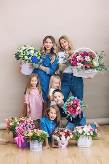Groep mensen gelukkige en mooie twee moeders en hun kinderen die bloemen bij elkaar houden