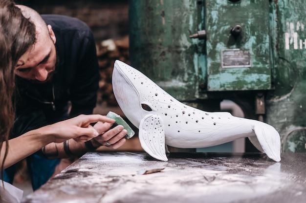Groep mensen genieten van favoriete baan in werkplaats. mensen werken zorgvuldig aan keramische walvissen