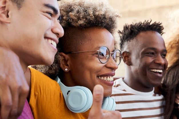 Groep mensen, glimlachend en blij om samen te zijn. een latina meisje knuffelt met haar vrienden, een afro-amerikaanse jongen en een aziatische jongen. concept van multi-etnische studenten.