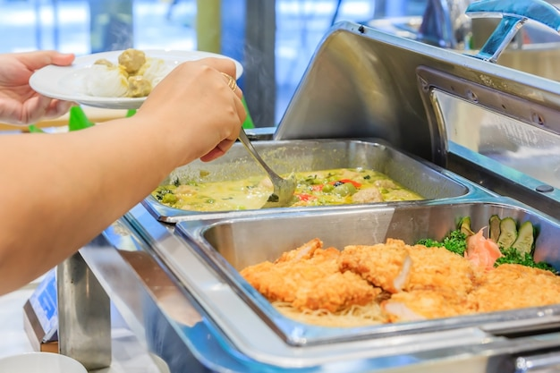Groep mensen in alles wat je kunt eten van het buffet eten binnen eten in een luxe restaurant