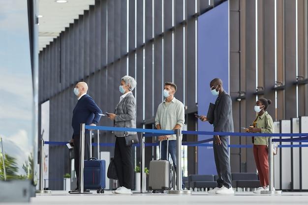 Groep mensen in beschermende maskers staan in een rij op de luchthaven