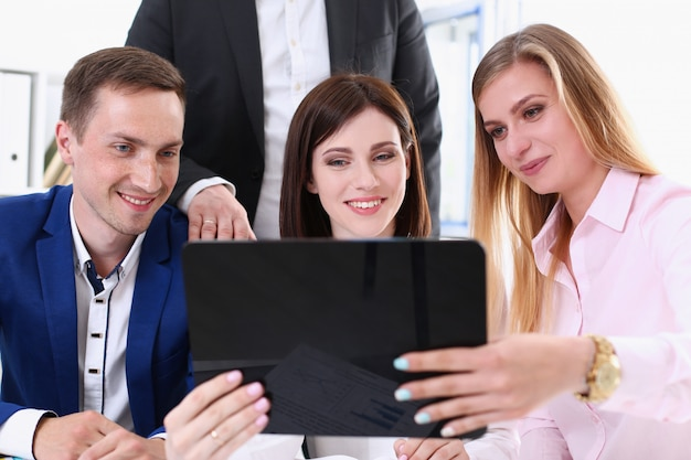 Groep mensen in kantoor kijken naar mobiele tablet-pc