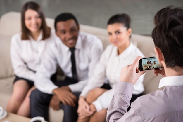 Groep mensen in kantoor tijdens pauze maken de foto.