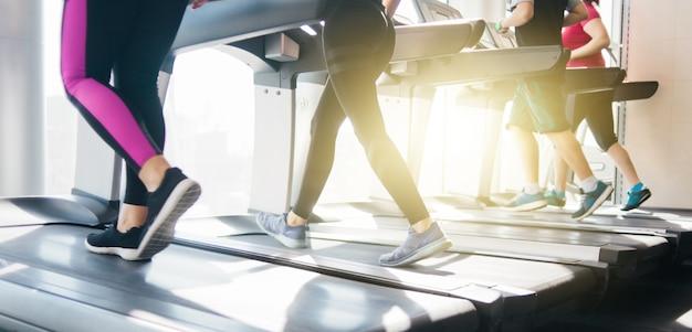 Groep mensen in sportkleding die op een tredmolen rondrennen. cardiotraining in de sportschool.