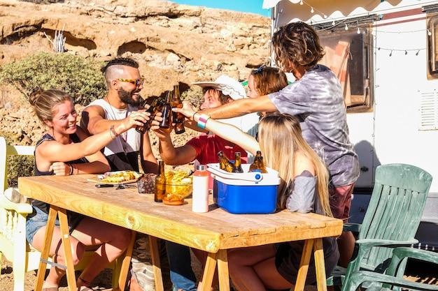Groep mensen jonge mannen en vrouwen samen met bieren roosteren in vriendschap buiten vrijetijdsbesteding