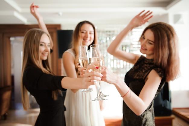 Groep mensen met champagne dansen op het feest.