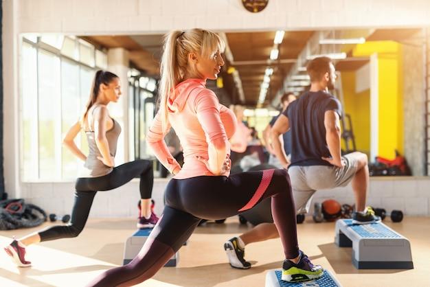 Groep mensen met gezonde gewoonten doen oefeningen voor benen op steppers. gym interieur.