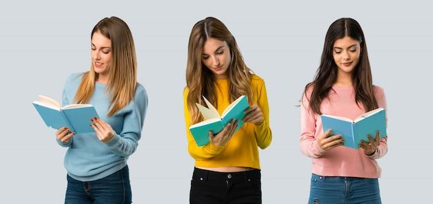 Groep mensen met kleurrijke kleren die een boek houden en van lezing op kleurrijke rug genieten