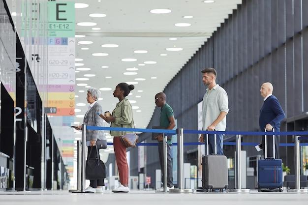 Groep mensen met koffers staan in een rij en wachten op het vertrek op de luchthaven