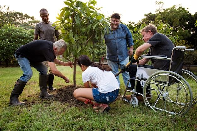 Groep mensen planten samen een boom buitenshuis