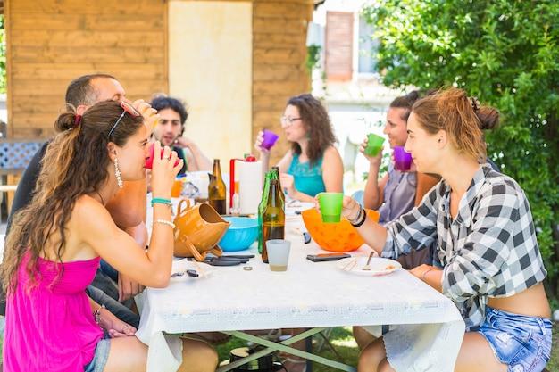 Groep mensen samen zitten en lunch hebben die drinken