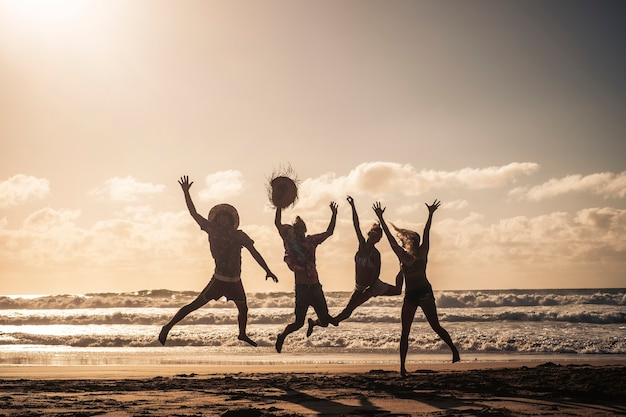 Groep mensen springen gelukkig samen op het strand tijdens zonsondergang met lucht en silhouetlichamen