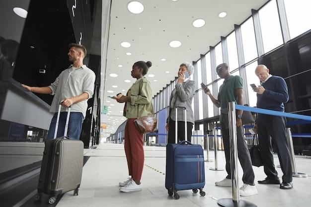 Groep mensen staan in een rij bij het loket op de luchthaven