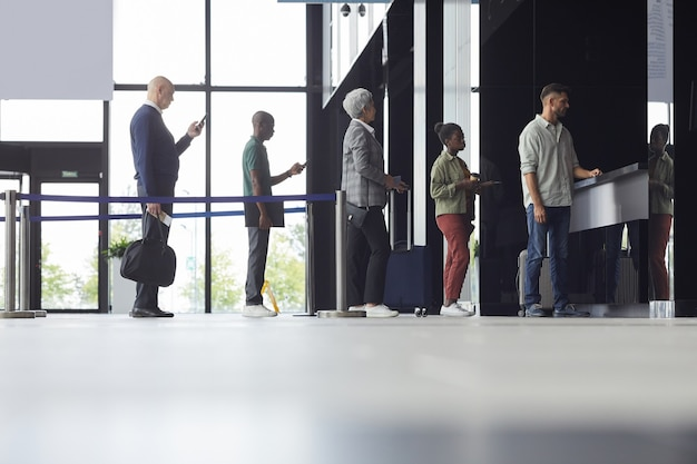 Groep mensen staan in een rij en kopen kaartjes voor het vliegtuig op de luchthaven