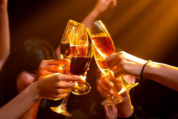 Groep mensen toast drankjes op feestje in dansclub Premium Foto