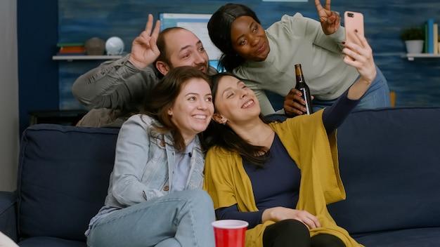 Groep mensen van gemengd ras die foto's maken met de telefoon terwijl ze op de bank zitten