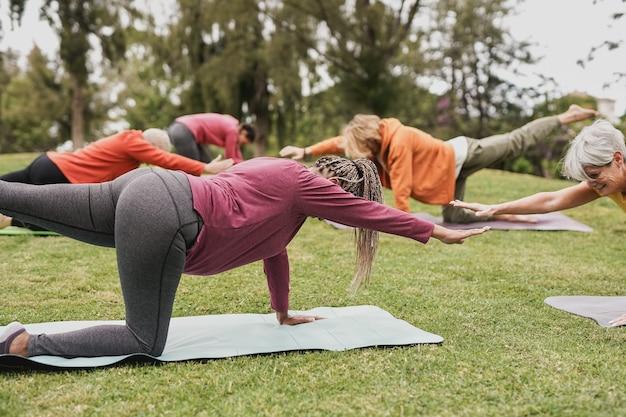 Groep mensen van meerdere generaties die yogales doen in het stadspark - focus op afrikaanse senior vrouw
