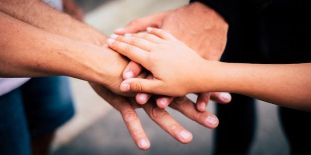 Groep mensen van verschillende leeftijden die elkaar aanraken en vasthouden als een teamconcept - familie en vrienden in de buitenlucht die de handen in elkaar slaan