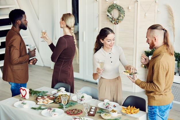 Groep mensen vieren kerstmis in de eetkamer