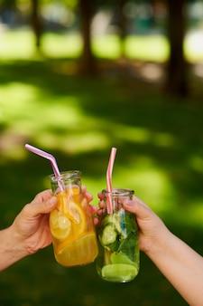 Groep mensen vieren met detox sap cocktails op groene natuur achtergrond