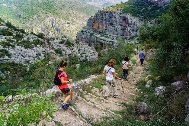 Groep mensen wandelen op het bergpad naar beneden trappen.