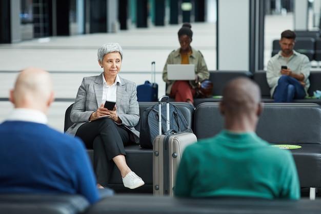 Groep mensen zitten in de wachtkamer en wachten op hun vlucht op de luchthaven