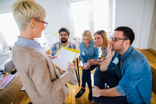 Groep mensen zitten in een cirkel op groepstherapie. kijkend naar hun therapeut en luisterend naar haar verhaal.