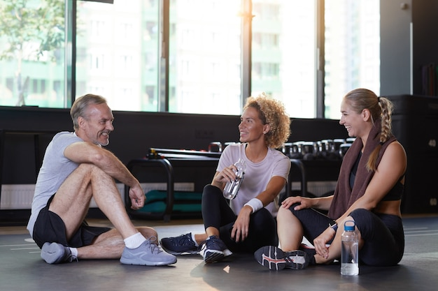 Groep mensen zittend op de vloer drinkwater en met elkaar praten na het sporten in de sportschool