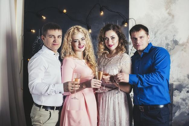 Groep mensenvrienden blij met een mooie glimlach en champagne om thuis samen kerstmis te vieren