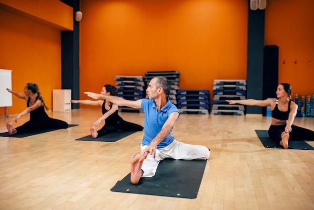 Groep met trainer zitten in yoga pose