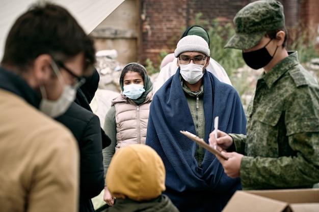 Groep migranten uit het midden-oosten met maskers die in de rij staan voor voedsel en medicijnen terwijl soldaat aantekeningen maakt