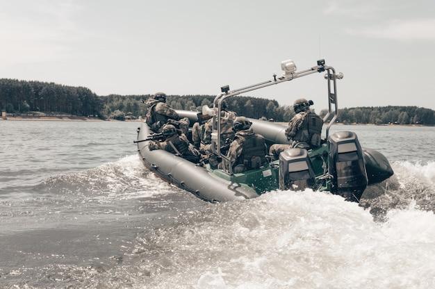 Groep militaire jagers op een boot met een flitser jagen piraten na.