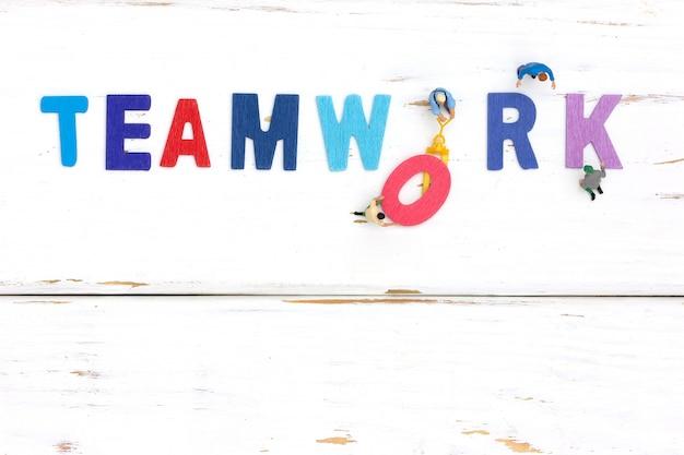 Groep miniatuurmensen die houten woordgroepswerk assembleren. bedrijfsconcept teamwerk.
