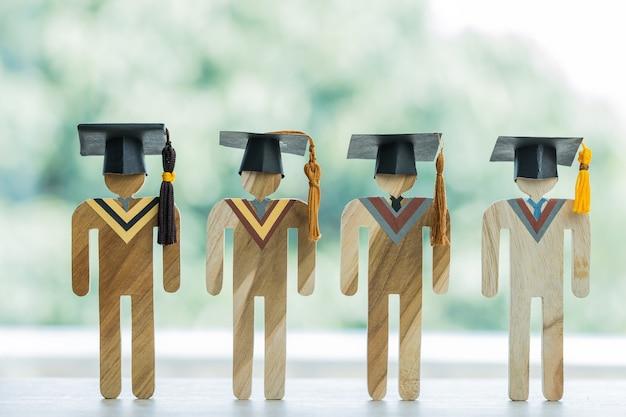 Groep modellen afgestudeerde feeststudenten die afstuderen dragen. concept van felicitaties voor succesvol onderwijs leren in universitaire prestaties en internationaal studeren in het buitenland. terug naar school