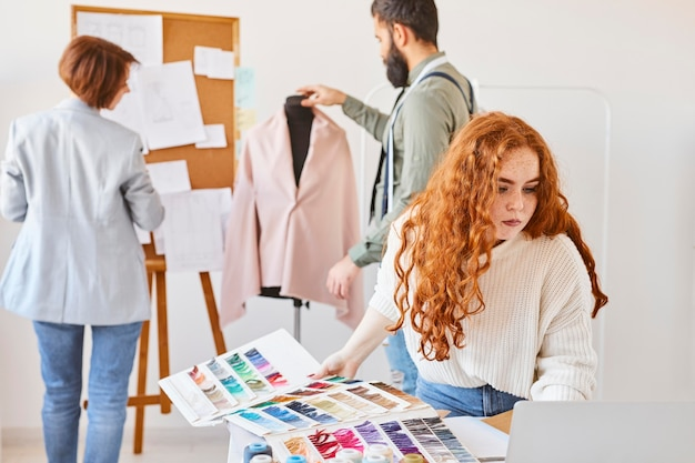 Groep modeontwerper werken in atelier met kleurenpalet en jurk vorm