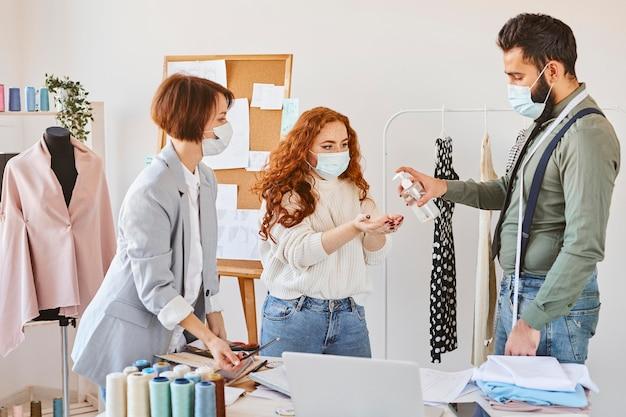 Groep modeontwerpers met medische maskers handen desinfecteren tijdens het werken in atelier