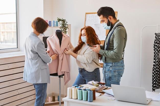 Groep modeontwerpers met medische maskers werken in atelier en kledingstuk op jurk formulier controleren