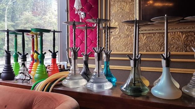 Groep modern glazen waterpijpapparaat op een houten standaard. restaurantbar. glazen waterpijpen op de bar in een café of bar gemaakt van prachtig veelkleurig glas. diffuus daglicht vanuit het raam.