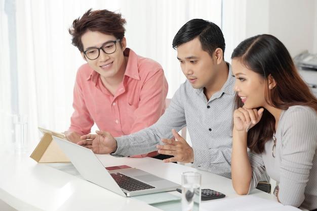 Groep moderne etnische medewerkers die op laptop letten