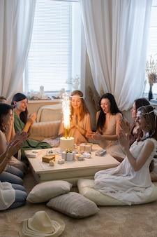 Groep moderne hippie vrouw handen klappen vieren verjaardag met petard flame cake vakantie